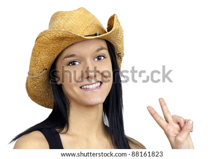 Pretty young cowgirl wearing a straw cowboy hat smiling and making the peace sign with her fingers. - stock photo