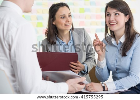 Pretty young creative woman having new idea for business project. Talking with colleagues during consultation - stock photo