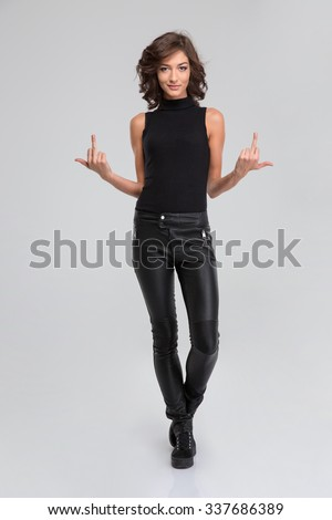 Pretty young curly attractive woman in black leather pants and top showing rude gesture with middle finger - stock photo