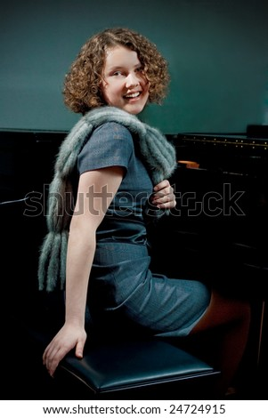 pretty young dark haired girl with curly hair sitting turned near piano smiling in grey dress with fur scarf smiling isolated - stock photo