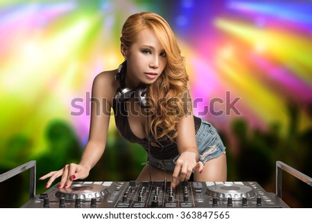 Pretty young disc jockey mixing music on turntables on stage with lights show at club party nightlife lifestyle. - stock photo