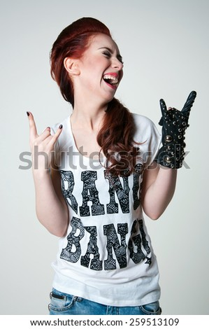 Pretty young emotional rock woman model with cute red haircut, wearing white top, ripped blue jeans, black leather glove with round metal rivets, shouting and screaming. Gray background - stock photo