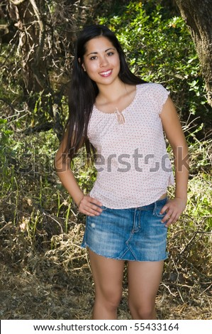 Pretty young Eurasian woman in the woods