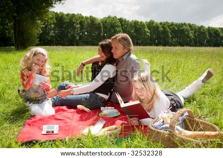 Pretty young family enjoying an outdoors picnic together in the field - stock photo