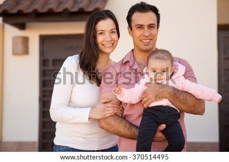 Pretty young family with a baby standing in front of their brand new house and smiling - stock photo