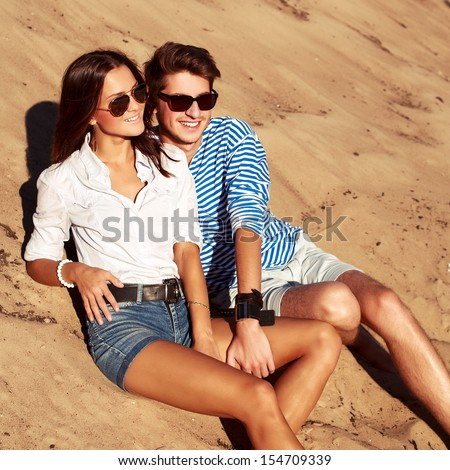 Pretty young fashion couple sitting on the beach having fun and looking at the sea in summer - stock photo