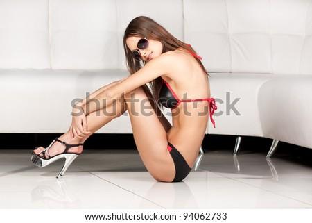 Pretty young fashion model in black bikini and sun glasses - stock photo