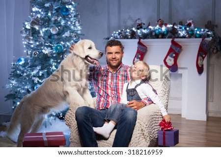 Pretty young father and his son are sitting on chair near Christmas tree. They are embracing and smiling. The boy is holding a box of gift. The man is stroking a dog - stock photo