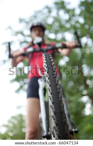 ... on her mountain bike (shallow DOF; selective focus) - stock photo