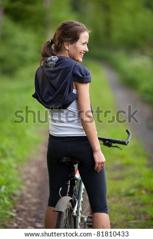 pretty young female biker outdoors on her mountain bike (shallow DOF; selective focus) - stock photo