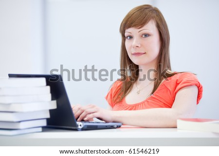 Pretty young female college student/researcher working on a laptop computer amid books - stock photo