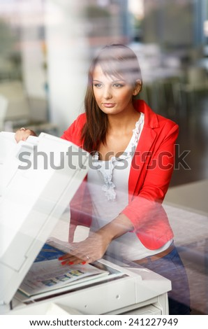 Pretty young female college student/secretary using a copy machine (shallow DOF; color toned image) - stock photo