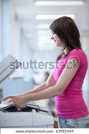 pretty young female college student using a copy machine (shallow DOF; color toned image) - stock photo