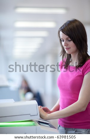 pretty young female college student using a copy machine (shallow DOF; color toned image)