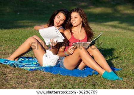 Pretty young female college students studying outdoors on a college campus.