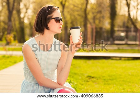 Pretty young female drinking coffee outside in the park and resting in the nature - stock photo