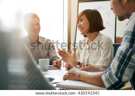 Pretty young female entrepreneur talking to her employees at meeting - stock photo