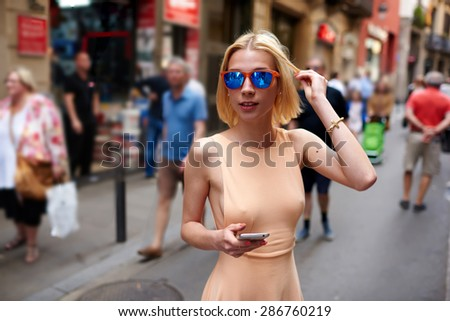 Pretty young female in summer dress and sunglasses walking down street with smart phone, attractive woman posing to the camera holding mobile phone, cute hipster girl with sexy body strolling outdoors - stock photo