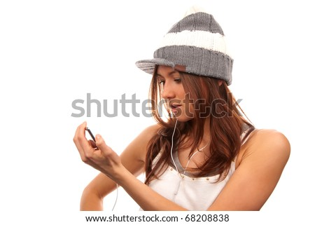 Pretty young female looking and reading text message on her new modern cell phone mobile and listening music in headphones isolated on a white background - stock photo