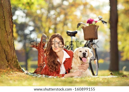 Pretty young female lying down with labrador retriever dog in a park - stock photo