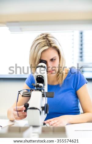 Pretty, young female optician/optometrist measuring new glasses she has prepared for a customer - stock photo
