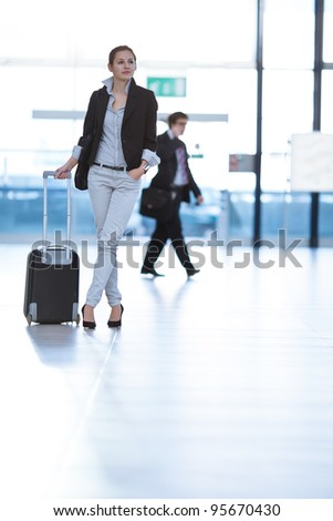 Pretty young female passenger at the airport (shallow DOF; color toned image) - stock photo