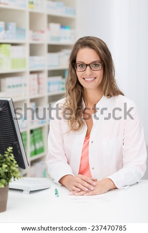 Pretty young female pharmacist standing behind her desk at the pharmacy smiling at the camera - stock photo