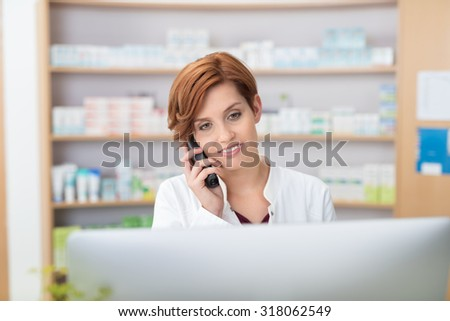 Pretty young female pharmacist talking on a telephone as she stands behind a computer in the pharmacy checking information with a smile