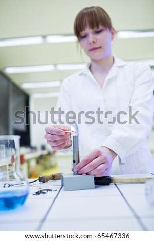 pretty, young female researcher lighting up a burner in a lab (shallow DOF; color toned image) - stock photo
