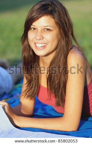 Pretty young female student studying outdoors on a college campus.