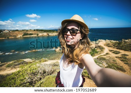 Pretty young female tourist takes travel selfie at the beach while summer vacation on Crete island in Greece - stock photo