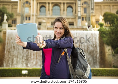Pretty young female tourist taking selfiein front of the fountain in Barcelona, Spain.