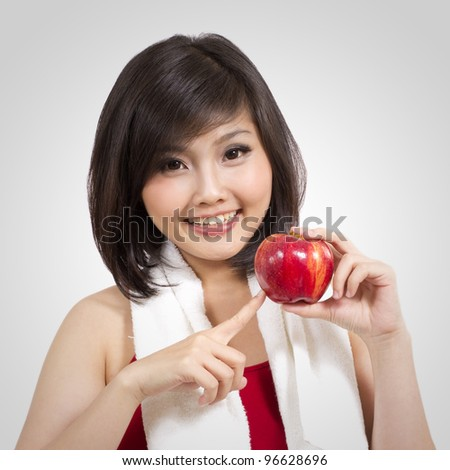 pretty young female with apple and towel after exercise - stock photo