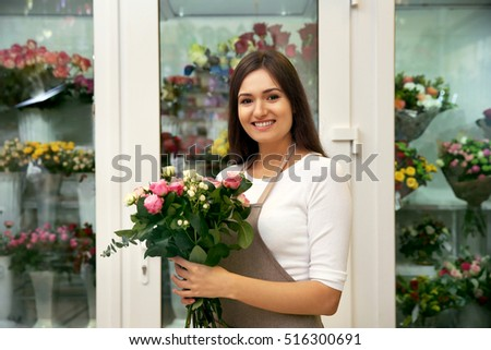 Pretty young florist with bouquet standing near flower shop