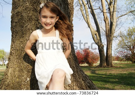 Pretty young girl at the park in white dress - stock photo