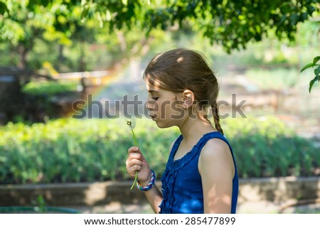Pretty young girl blowing a dandelion clock in the garden with a rainbow on a sprinkler in the background making a colorful arc behind her - stock photo