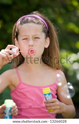 Pretty young girl blowing soap bubbles outdoor (the sun is reflecting in the bubbles) - stock photo
