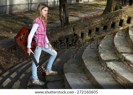 Pretty Young Girl Casually Dressed with Guitar in Her Hand Walking Up the Stairs in the Park on Sunny Day - stock photo