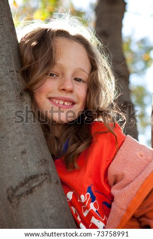 Pretty young girl climbing tree and smiling - stock photo