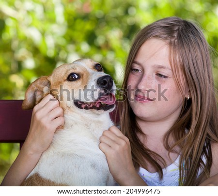 Pretty young girl cuddling cute dog in park - stock photo