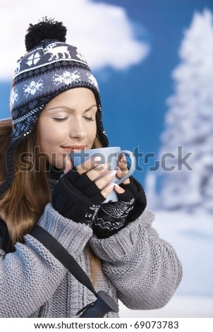 Pretty young girl dressed up warm for skiing wearing cap and gloves drinking hot tea eyes closed front of winter landscape . - stock photo
