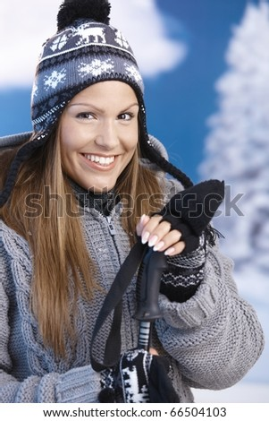 Pretty young girl dressed up warm for skiing wearing cap and gloves smiling front of winter landscape .? - stock photo