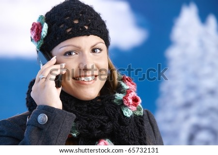 Pretty young girl dressed up warm in coat, cap and scarf, smiling front of winter landscape using mobile phone .? - stock photo