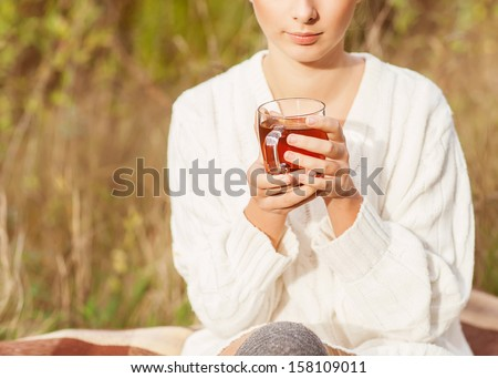 Pretty young girl drinks tea in retro clothes, enjoying autumn day - stock photo