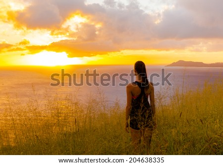 Pretty young girl enjoying sunset in Hawaii.  - stock photo