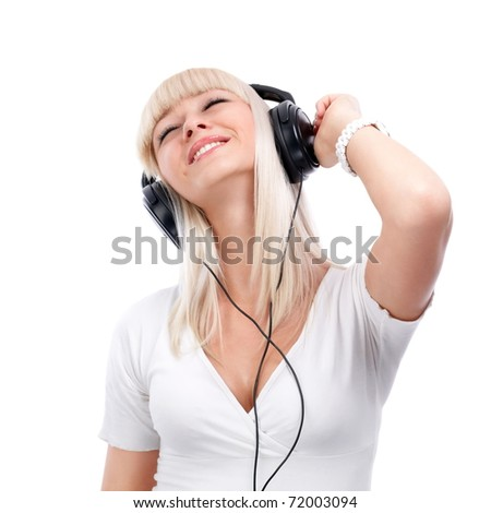 Pretty young girl enjoys listening music - stock photo