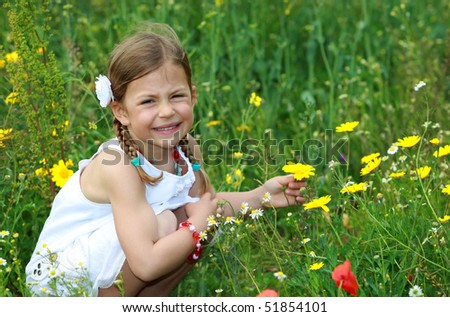 Pretty young girl holding a daisy flower in a meadow