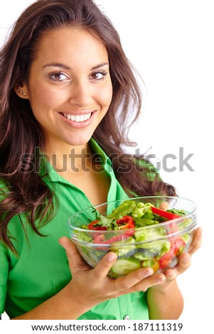 Pretty young girl holding bowl of fresh vegetable salad and looking at camera - stock photo