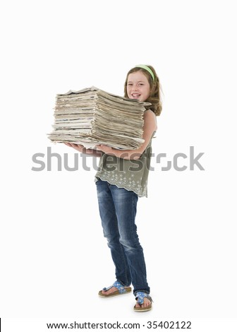 Pretty, young girl holding pile of old newspapers for recycling - stock photo