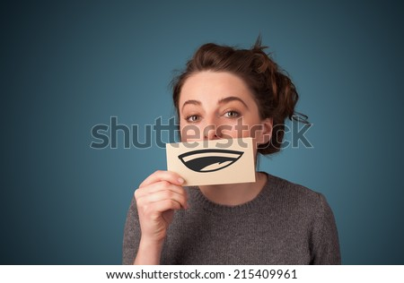 Pretty young girl holding white card with smile drawing on gradient background